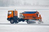 stock photo of icy road  - Truck deicing a road in winter - JPG
