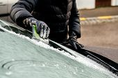 Woman Cleaning Car Windshield From Frost Using Specialized Ice Frost Scraper And Rubber Squeegee Car poster