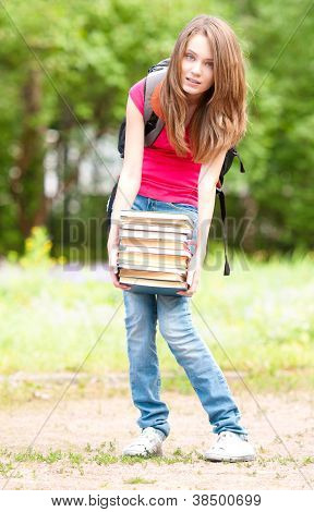 Young Student Girl Holding Big Pile Of Heavy Books
