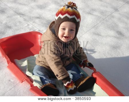 Little Boy On Red Sled In The Snow