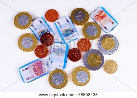 Euro bills and coins made of chocolate white background soft shadows