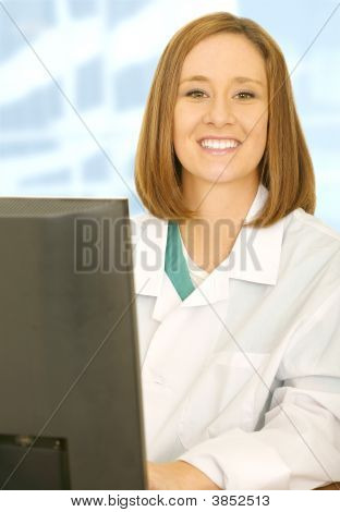 Happy Doctor On Her Desk Looking At Camera