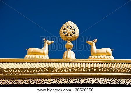 Tibetan Monastery Gates. Buddhist Symbols: Dharma-wheel And Deer On Decorated Roof Under Blue Sky At