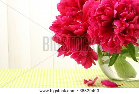 beautiful pink peonies in glass vase on table on white wooden background