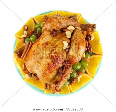 whole roasted chicken with grapes, oranges and spices on blue plate isolated on white