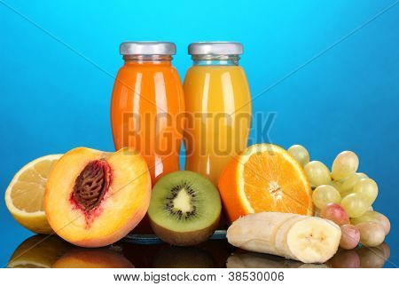 Delicious multifruit juice in a bottle and fruit next to it on blue background