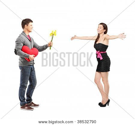 Full length portrait of a man giving a red heart and flowers to his girlfriend isolated on white background