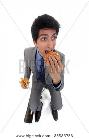 Businessman scoffing a burger and fries