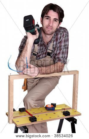 Man posing with his workbench and holding an electric screwdriver