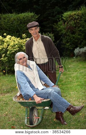 Older couple messing around with a wheelbarrow