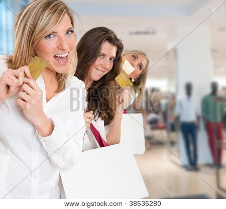 Three young women in a happy shopping expedition with credit cards