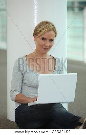 Mujer sentada al lado de la columna usando la computadora portátil