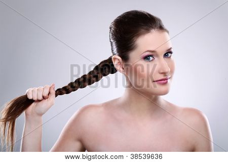 Beautiful woman holding her hair tress over gray background
