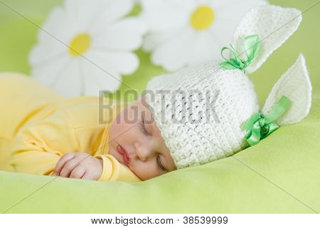 sleeping baby in funny rabbit hat on green background
