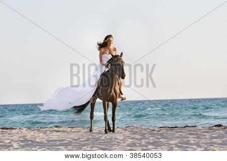 young beautiful woman in white dress riding horse on sea background