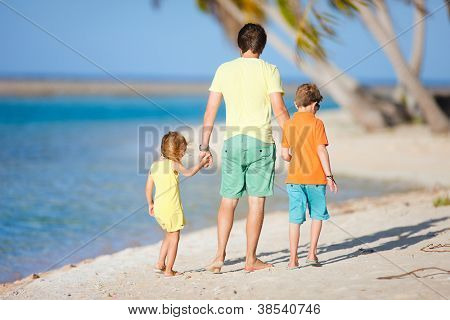 Father and kids walking on a deserted tropical beach