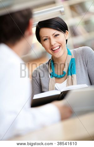 Pretty woman communicates with man showing her something in the book sitting at the desk at the library