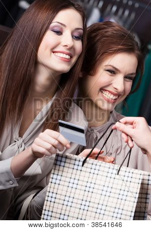 Pretty women pay for purchases with credit card