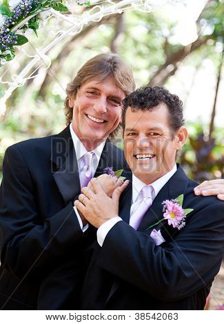 Handsome gay couple pose for portrait on their wedding day.