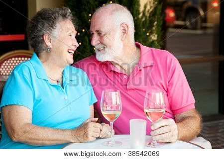 Senior couple flirting and laughing together over a glass of white wine.