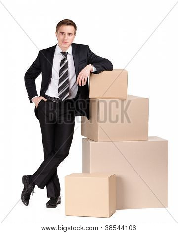 Manager in suit stands near pile of pasteboard boxes, isolated on white