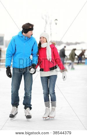 Romantic young couple in warm winter clothing holding hands and smiling at each other while ice skating.