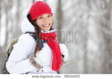 Woman winter hiking. Beautiful young Asian woman enjoying the falling snow dressed in a cheerful red winter scarf and cap and with a satchel on her back with copyspace.
