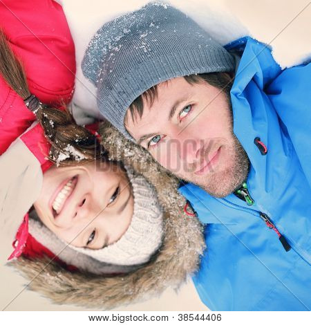 Winter couple happy. Overhead view of the heads of happy attractive interracial Asian / Caucasian couple lying in snow in warm winter clothing