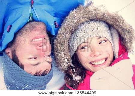 Happy winter couple. Cropped view of the faces of a joyful young interracial Asian / Caucasian couple lying on their backs in snow with their heads close together.