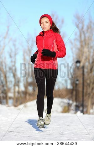 Sport woman running in winter. Female runner portrait in full body jogging in snow on cold winter day. Multiracial Asian Chinese / Caucasian fitness girl.