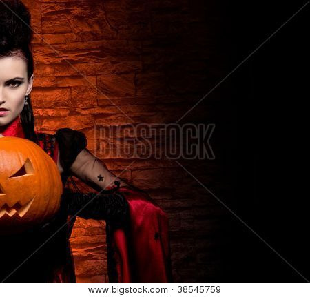 Halloween concept: young and sexy lady vampire in the dungeon