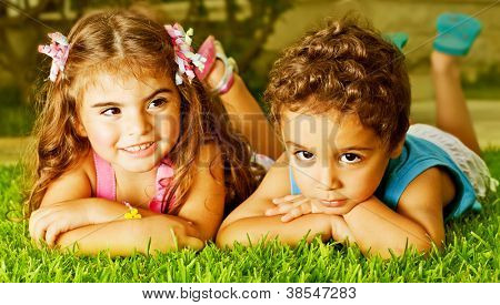 Picture of two happy kids laying down on fresh green grass, brother and sister enjoying summer holiday, cute girl and pretty boy having fun outdoors, happy friends playing on backyard