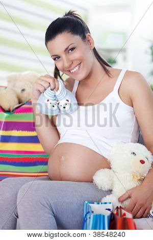 cheerful pregnant woman shoving bought things for your baby