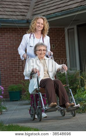 Home Care Nurse Pushing Senior on Wheelchair Outdoor in Early Morning