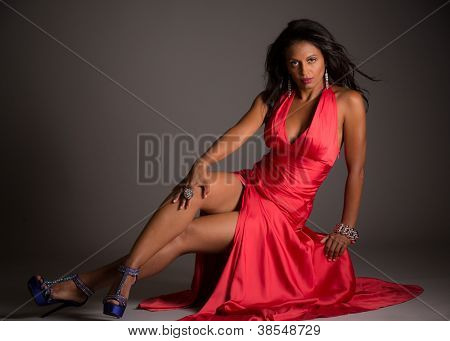 African American Female Model Portrait Low Key on Grey Background Wearing Red Dress