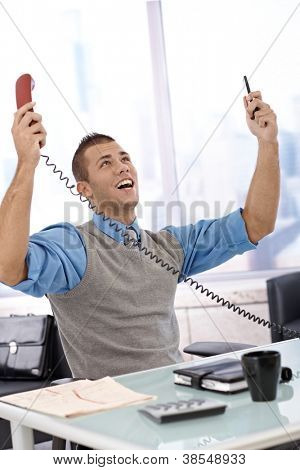 Happy businessman sitting at desk with arms raised, laughing, looking up, holding landline and mobile phone, celebrating.