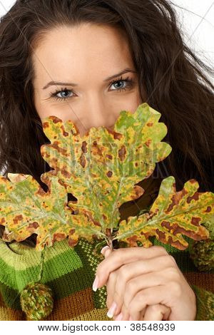 Closeup portrait of smiling woman hiding behind beautiful autumn tree leaf.