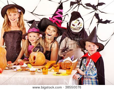 Halloween party with children holding carving pumpkin.
