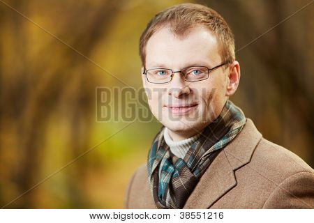 Portrait of elegant young man wearing coat and scarf looking at camera in autumn