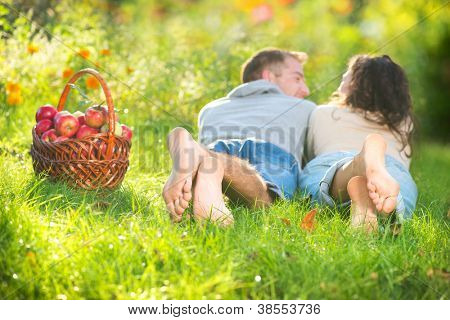 Happy Couple Relaxing on the Grass and Eating Apples in Autumn Garden.Healthy Food.Outdoor?.Park.Basket of Apples.Harvest concept