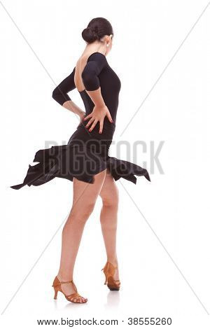 back view of a young salsa woman dancer in action with hands on hips. Isolated on white