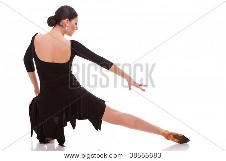back view of a beautiful salsa dancer posing in a lunge dance move