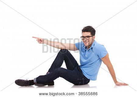 casual young man sitting on the floor and pointing to his side while looking at the camera with a smile on his face. isolated on white