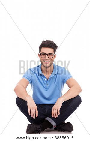 young casual man with eyeglasses sitting on the floor in the lotus position and smiling