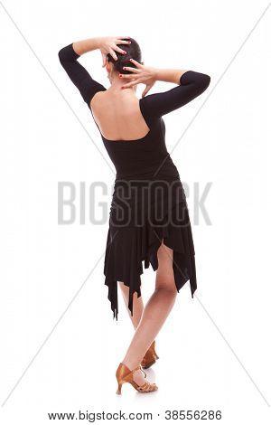 Vista traseira de um dançarino de salsa jovem segurando-lhe as mãos na parte de trás de sua cabeça, em uma pose de dança