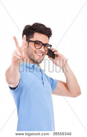 Handsome young casual man talking on the phone and showing peace sign while looking at the camera. isolated on white