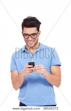 picture of a young casual man writing an sms and laughing. young man with eyeglasses laughing while reading something on the phone.