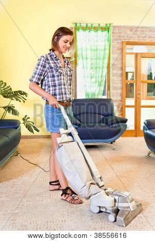 House work, young beautiful woman with vacuum cleaner at home. Housework concept