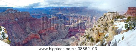 Grand Canyon panorama view in winter with snow and clear blue sky.