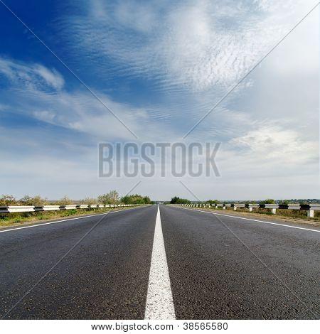 primer plano de la carretera bajo el nublado cielo azul